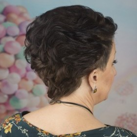 Волосы уложены назад плойкой, полуволнистые , сделан небольшой начес, что дает стойкость укладки.