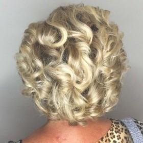 Волосы средней длинны или ближе к коротким волосам , уложены в объеме и волнами или локонами слегка раскрученными . Что дает романтику , нежность , сексапильность маме невесты. Короткая челка легкими прядями ложится на лицо и часть уходит в причёску, давая плавный переход. Все волосы убраны от лица , что тоже данную модель освежает и молодит