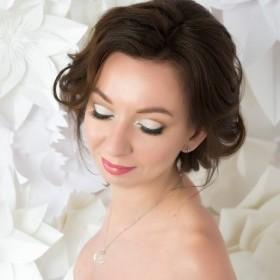 Свадебная прическа. убранная в пучек на затылке. Около лица волосы объемные, челочная зона лежит свободно, объемно, зачесана набок.