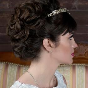Свадебная прическа с густой челкой, объемная, с гладкой текстурой. Объем по всему затылку. Волосы выложены гладкими волнами.