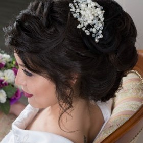 Свадебная прическа из полудлинных волос, сделана с использованием валика.Прическа объемная, пряди выложены волнами.