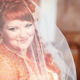 В свадебном макияже к рыжим волосам и к оранжевой накидке тени выбраны: золотые, оранжевые и зеленые разных оттенков. Макияж выполнен в стиле кошачий глаз и петля, что увеличивает глаза, делая их яркими, а лицо более пропорциональным.