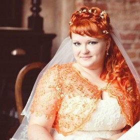 Свадебная прическа с короткой косой челкой. Высота прически и объем исполнена буклями. В прическе живые цветы-гипсофила.
